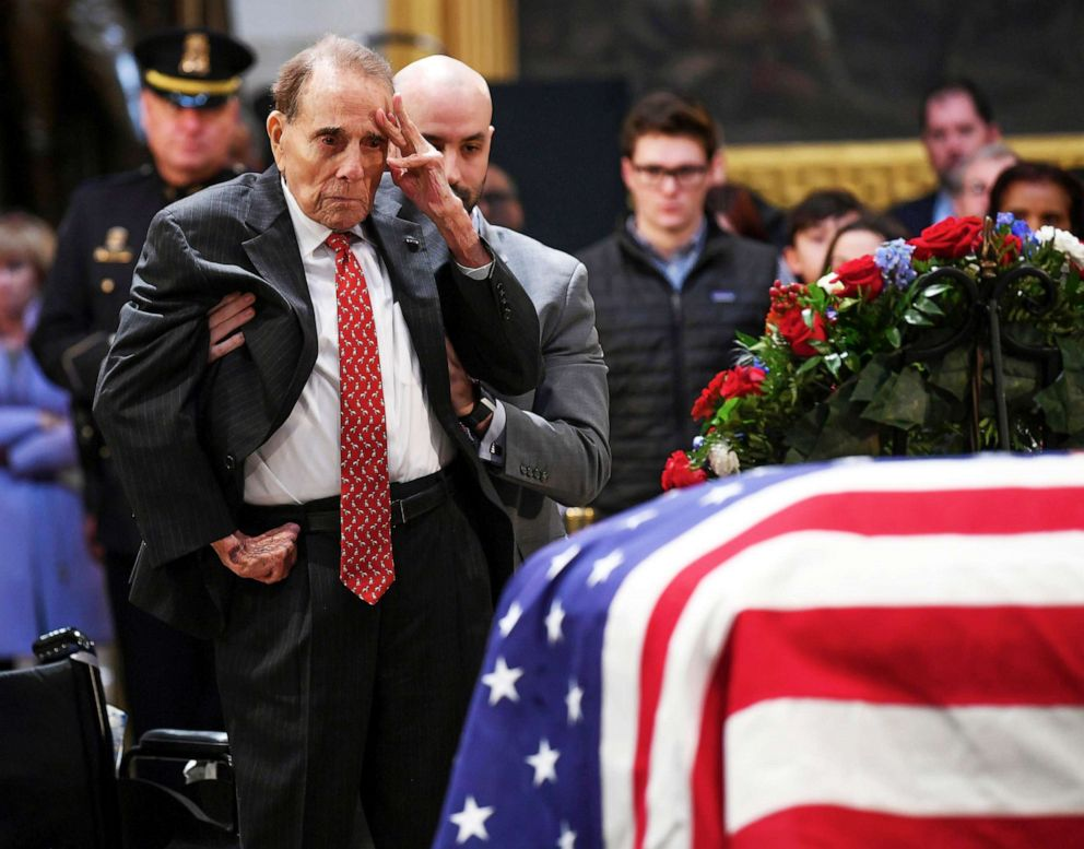 Former Sen. Bob Dole salutes the casket of President George H.W. Bush who lies in state at the U.S. Capitol Rotunda in Washington D.C., Dec. 4, 2018.