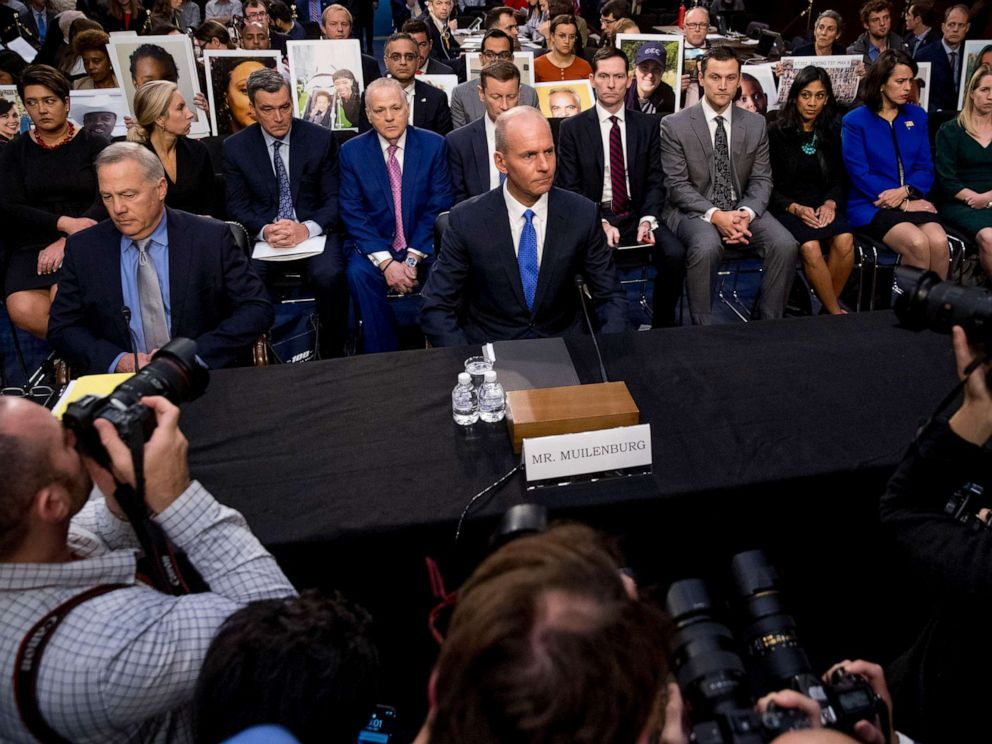 PHOTO: Survivors of those killed in the Ethiopian Airlines Flight 302 and Lion Air Flight 610 crashes hold photos of their family members behind Dennis Muilenburg, center, and John Hamilton, left, on Capitol Hill in Washington, Oct. 29, 2019.