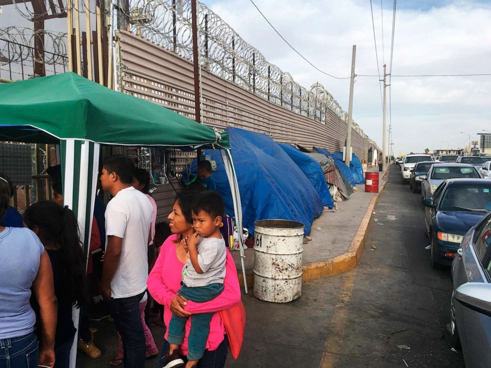 PHOTO: Migrants walk between tents, left, and cars waiting to cross the border between Mexico, and Arizona, May 5, 2019. The tent slots are for families about to be called, allowing them to be ready on a moments notice.