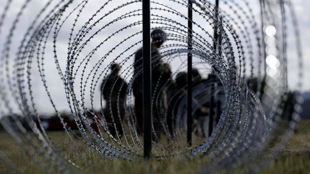 In this Nov. 3, 2018, file photo, members of the U.S. Army build a razor wire fence around area for tents near the U.S.-Mexico International bridge, in Donna, Texas.