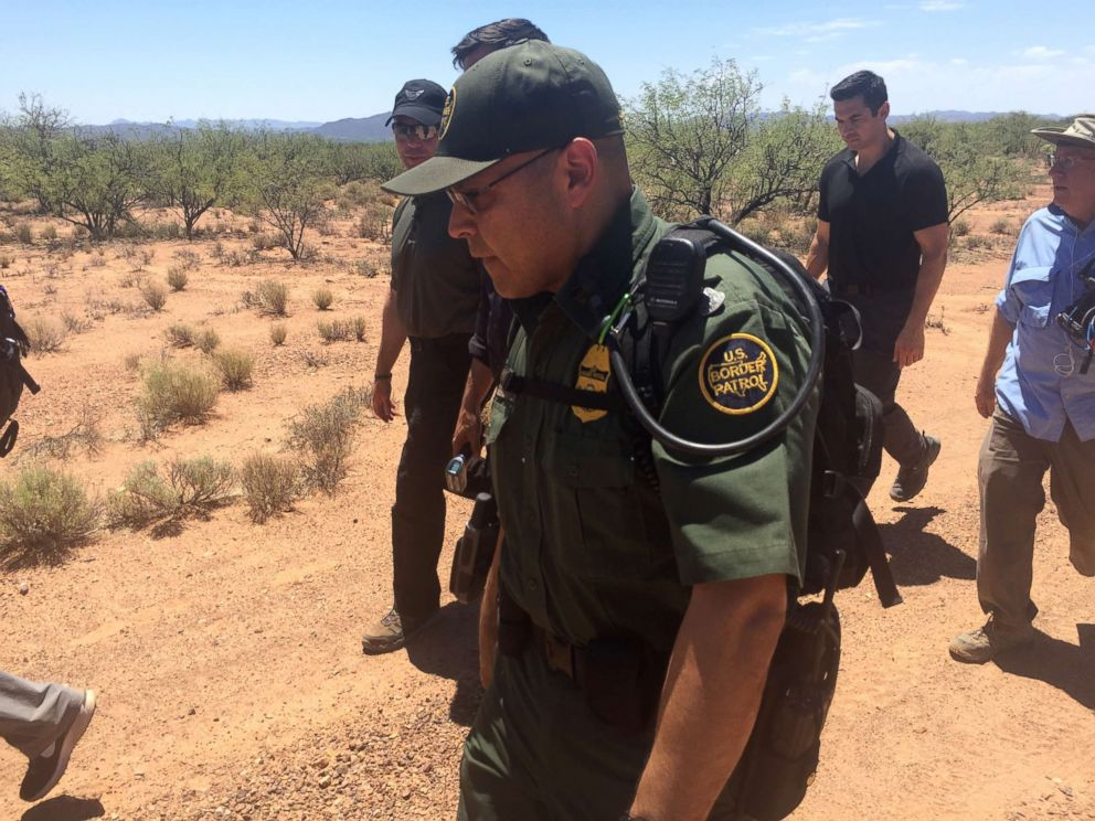 PHOTO: Customs and Border Protection Commissioner Kevin McAleenan, in sunglasses and hat, walks with a Border Patrol agent and an ABC News crew through the desert along the Arizona border. June 27, 2018.