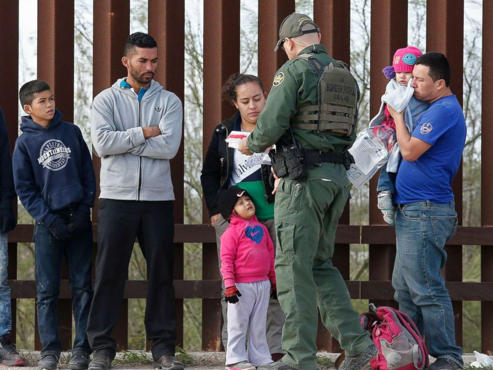 PHOTO: Families that crossed the border to enter the United States illegally turn themselves in to Border Patrol agents next to a fence along the Rio Grande River near McAllen, in Texas, Jan. 23, 2019.