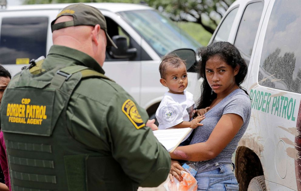 PHOTO: A mother migrating from Honduras holds her 1-year-old child after surrendering to U.S. Border Patrol agents for illegally crossing the border near McAllen, Texas, June 25, 2018.