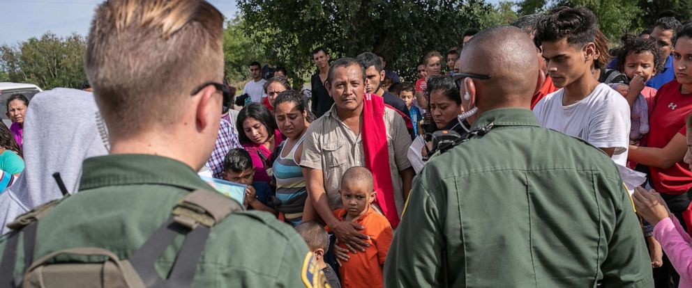 PHOTO: U.S. Border Patrol agents watch over immigrants after taking them into custody on July 02, 2019, in Los Ebanos, Texas.