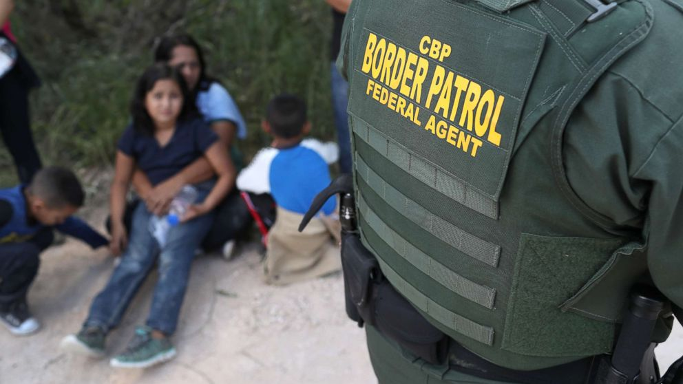 """Central American asylum seekers wait as U.S. Border Patrol agents take them into custody, June 12, 2018 near McAllen, Texas. The families were then sent to a U.S. Customs and Border Protection (CBP) processing center for possible separation. U.S. border authorities are executing the Trump administration's """"zero tolerance"""" policy towards undocumented immigrants. U.S. Attorney General Jeff Sessions also said that domestic and gang violence in immigrants' country of origin would no longer qualify them for political asylum status."""