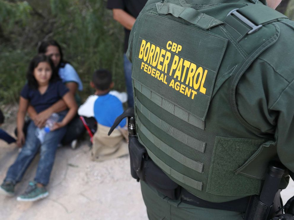 PHOTO: Central American asylum seekers wait as U.S. Border Patrol agents take them into custody, June 12, 2018 near McAllen, Texas.