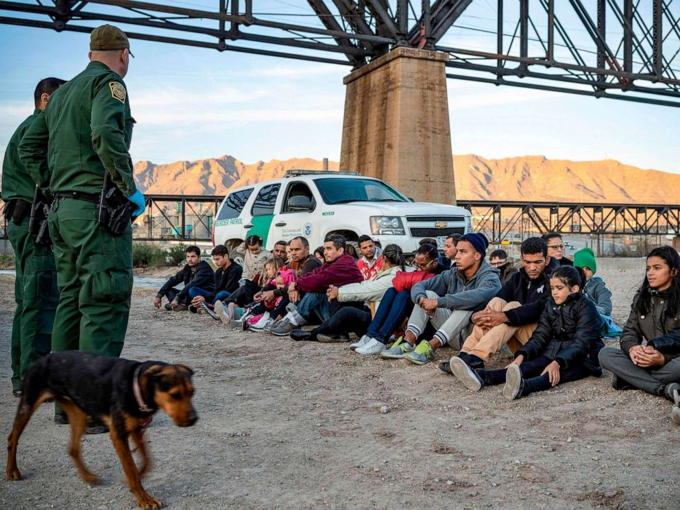 PHOTO: (A group of migrants, who had just crossed the border, sit on the ground near U.S. Border Patrol agents on the US-Mexico border in Sunland Park, N.M., March 20, 2019.