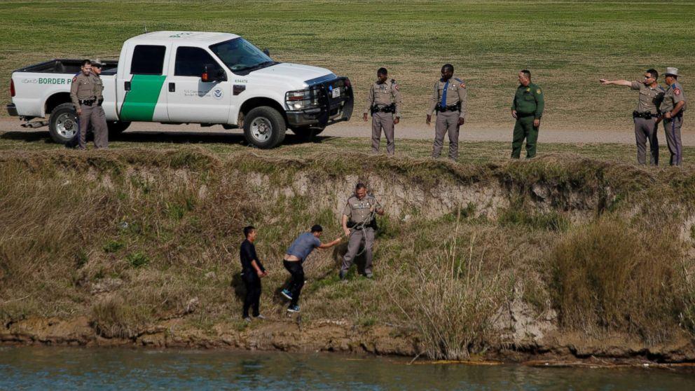 U.S. border patrol agents receive migrants after crossing the Rio Bravo, seen from Piedras Negras, Mexico, Feb. 20, 2019.