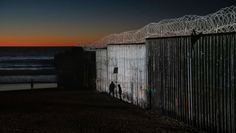 The sun sets while people walk close to the border fence between the U.S. side of San Diego, Calif., and Tijuana, in Mexico, Jan. 2, 2019.