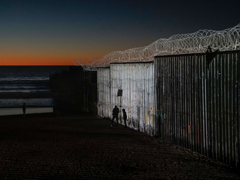 PHOTO: The sun sets while people walk close to the border fence between the U.S. side of San Diego, Calif., and Tijuana, in Mexico, Jan. 2, 2019.