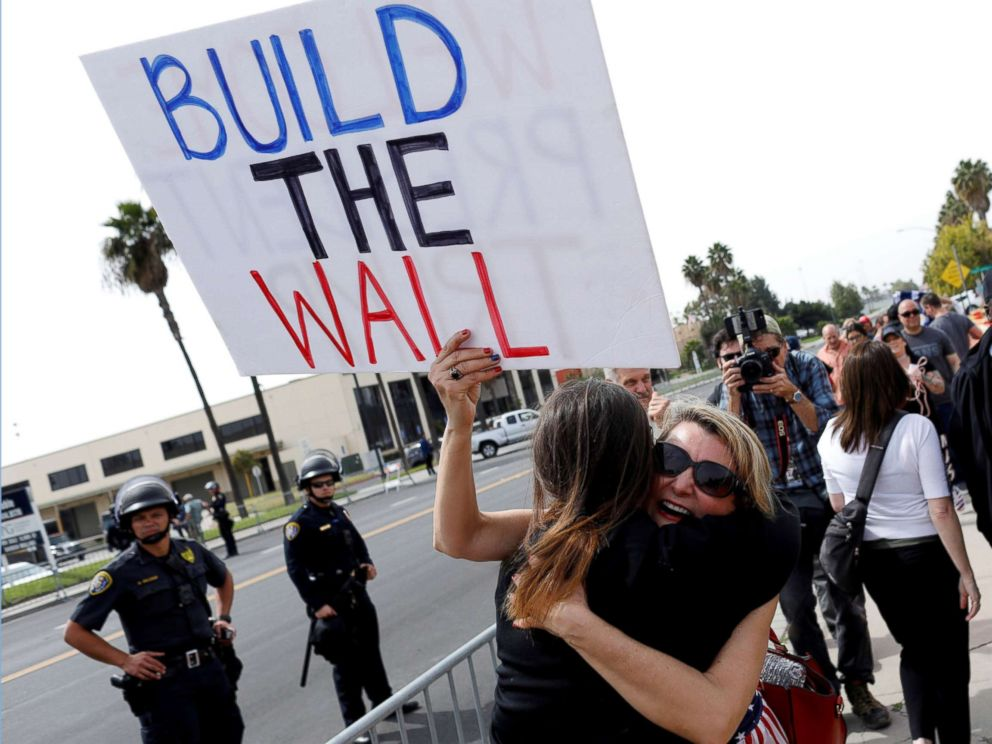 PHOTO: Supporters hug after President Donald Trumps motorcade drove past them following his viewing of border wall prototypes in San Diego, March 13, 2018.