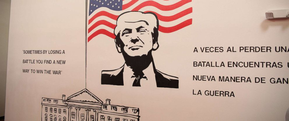 Murals of presidents and their quotations are plastered on the walls of a Walmart-turned-shelter for almost 1,500 undocumented children.