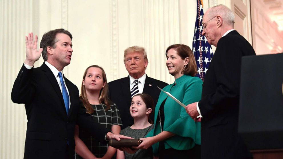 Retired Justice Anthony Kennedy, right, ceremonially swears-in Supreme Court Justice Brett Kavanaugh, as President Donald Trump looks on, in the East Room of the White House, Oct. 8, 2018. Ashley Kavanaugh holds the Bible and daughters Margaret, left, and Liza, look on.
