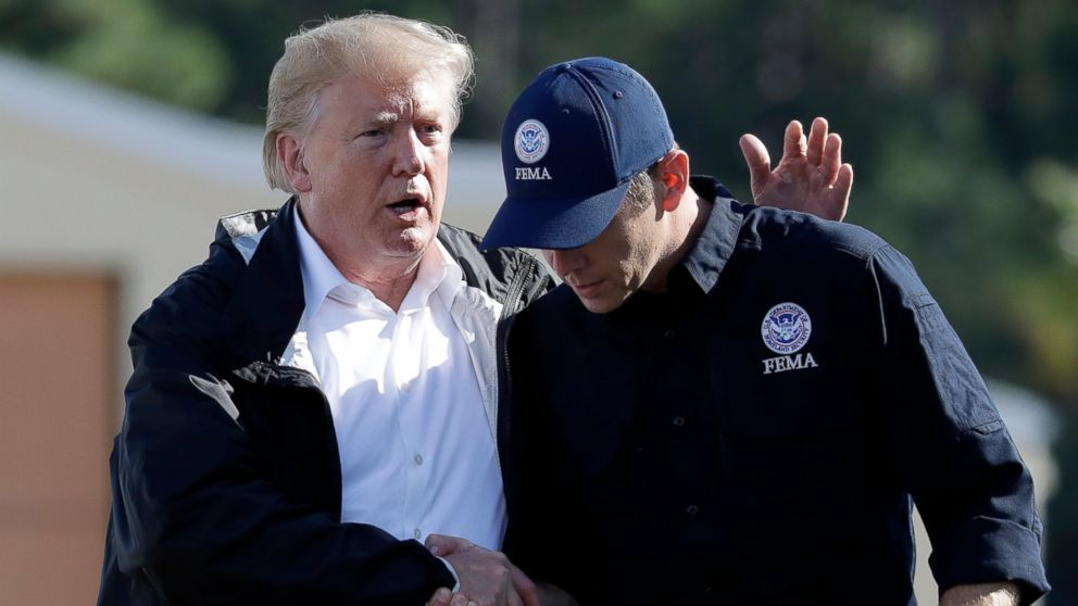President Donald Trump shakes hands with FEMA Administrator Brock Long after visiting areas in North Carolina and South Carolina impacted by Hurricane Florence, Wednesday, Sept. 19, 2018, at Myrtle Beach International Airport in Myrtle Beach, S.C.