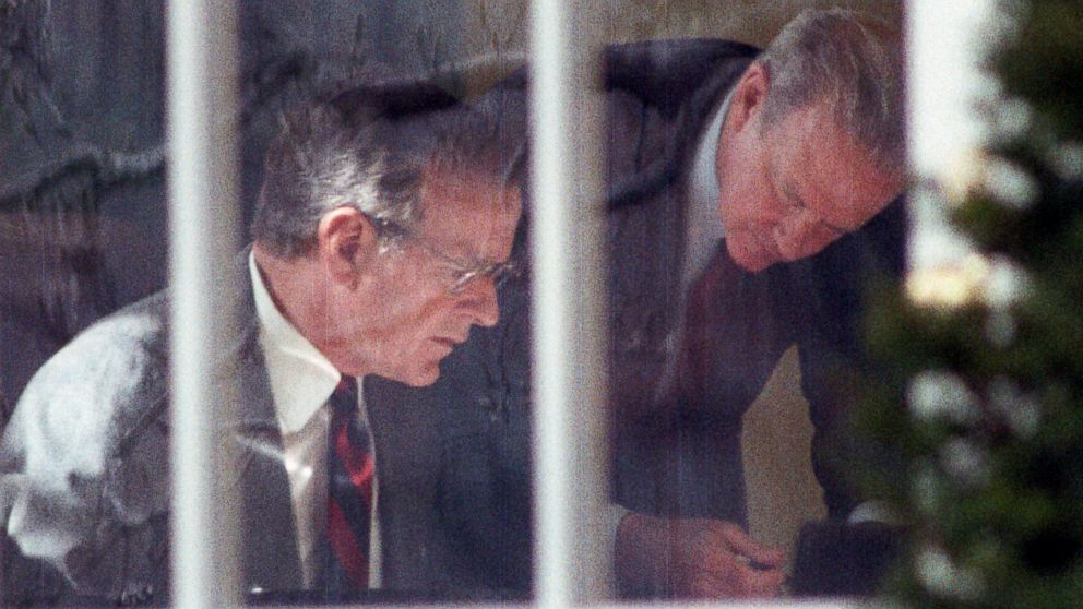 President George H.W. Bush and Secretary of State James Baker study prepared remarks at Bush's desk in the Oval Office, Feb. 22, 1991.