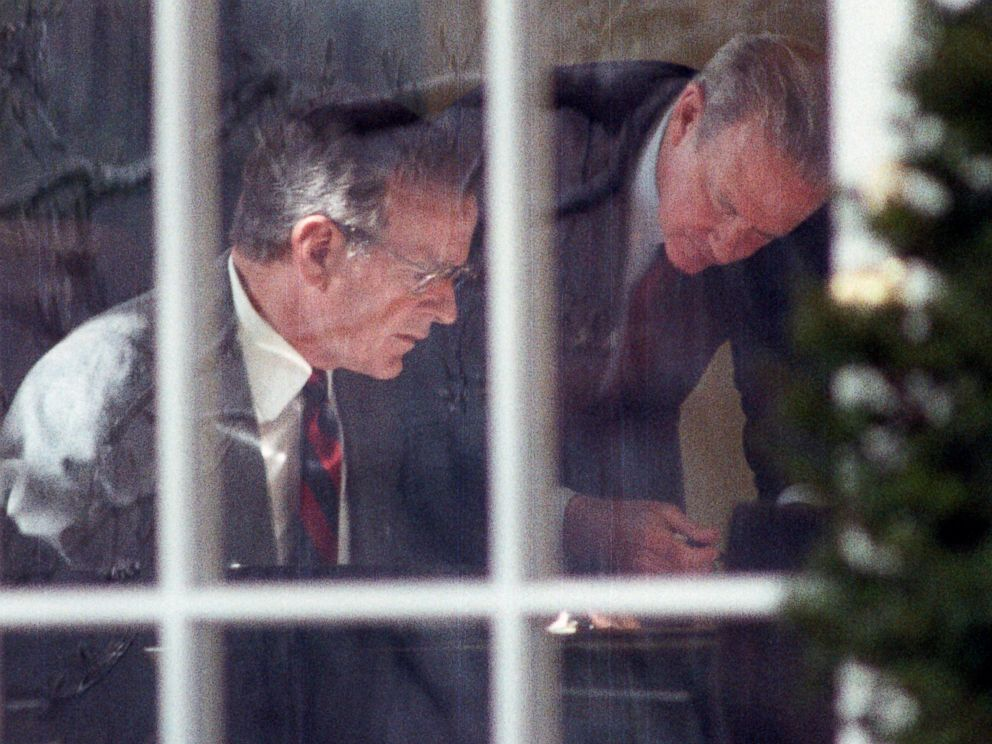 PHOTO: President George H.W. Bush and Secretary of State James Baker study prepared remarks at Bushs desk in the Oval Office, Feb. 22, 1991.