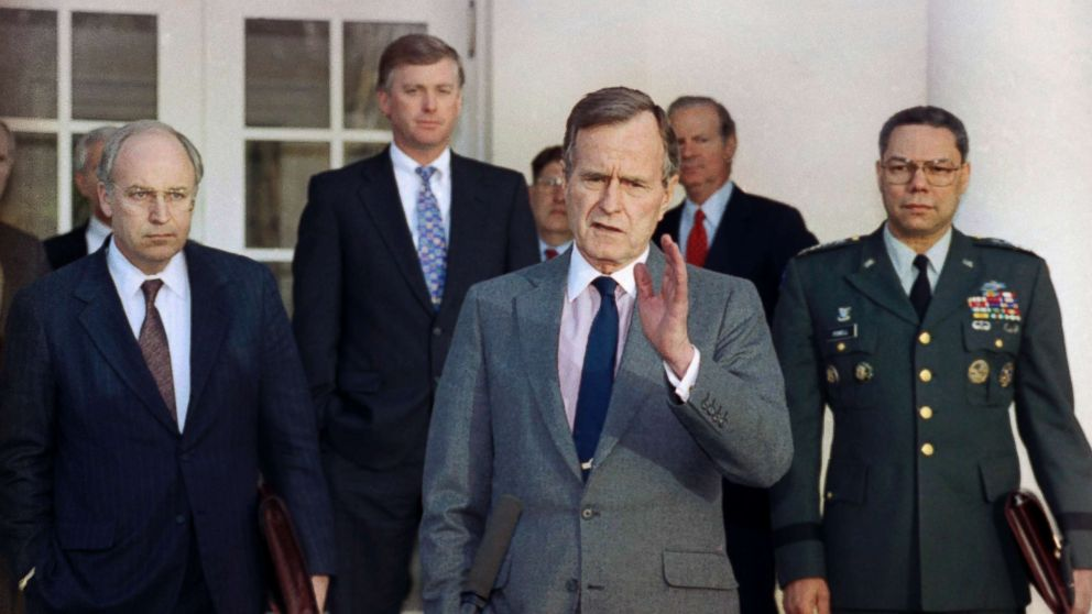 President George H.W. Bush talks to reporters in the Rose Garden of the White House after meeting with top military advisors to discuss the Persian Gulf War. From left are, Defense Secretary Dick Cheney, Vice President Dan Quayle, White House Chief of Staff John Sununu, the president, Secretary of State James A. Baker III, and Joint Chiefs Chairman Gen. Colin Powell.