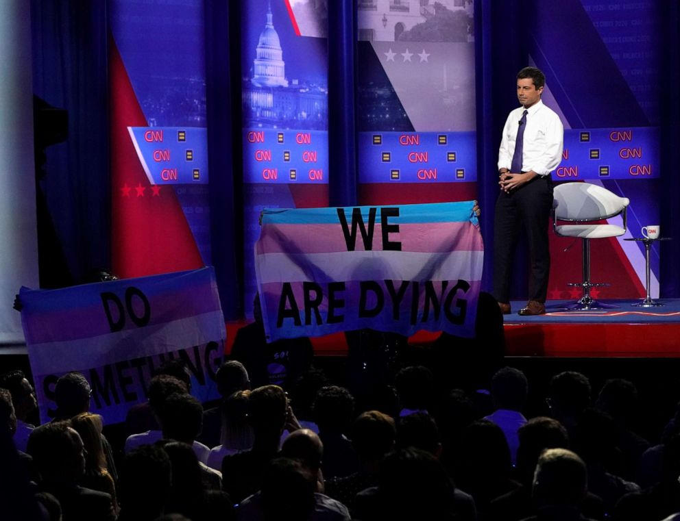 PHOTO: Democratic 2020 U.S. presidential candidate South Bend, Indiana, Mayor Pete Buttigieg looks on as protesters hold a banner in a televised town hall on CNN dedicated to LGBTQ issues in Los Angeles on Oct. 10, 2019.