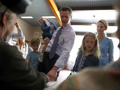 PHOTO: Democratic California gubernatorial candidate Lt. Gov. Gavin Newsom with his children and his wife, Jennifer Siebel Newsom sign in to vote at the Masonic Temple Fairfax on June 5, 2018 in Larkspur, California.