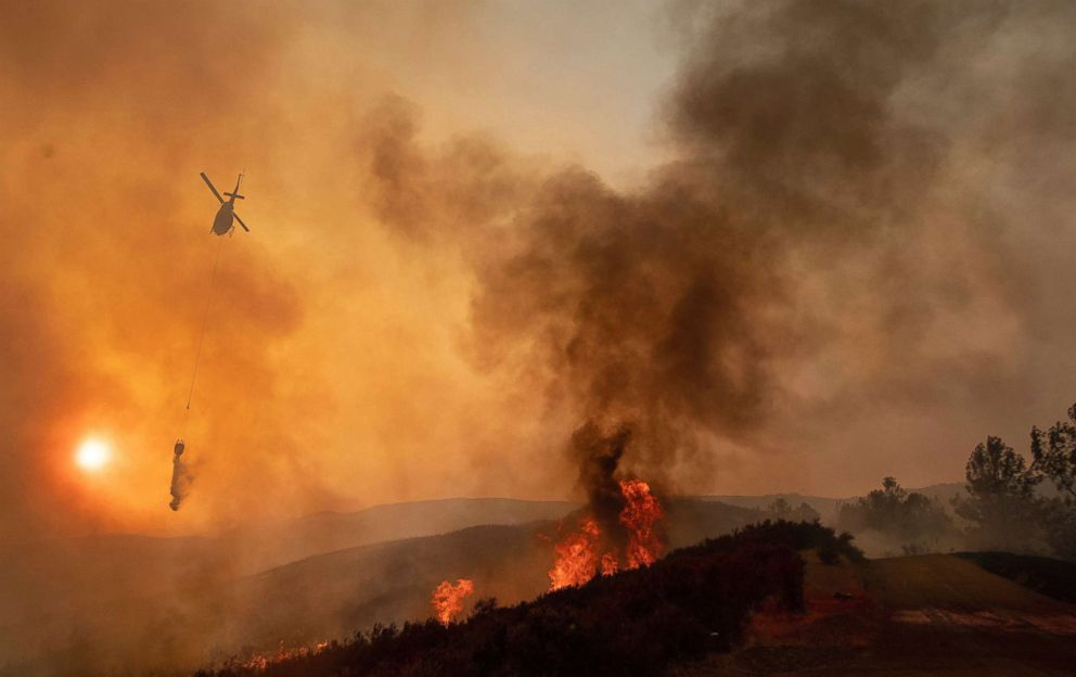 PHOTO: A helicopter drops water on a burning hillside during the Ranch Fire in Clearlake Oaks, Calif., Aug. 5, 2018.