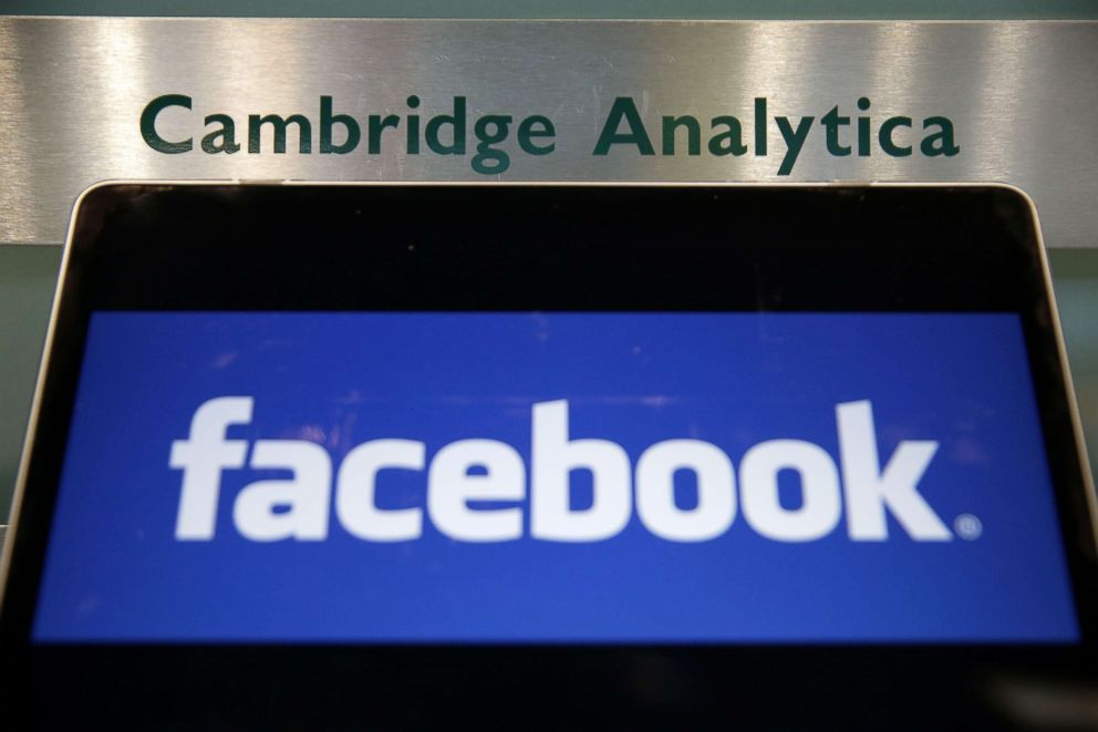 A laptop showing the Facebook logo is held alongside a Cambridge Analytica sign at the entrance to the building housing the offices of Cambridge Analytica, in central London, March 21, 2018.