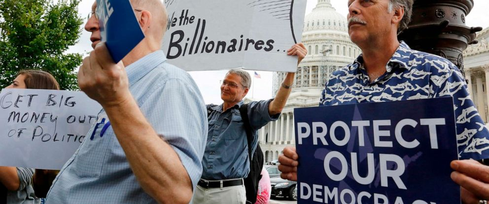 PHOTO: Supporters of a proposed constitutional amendment for campaign finance reform hold signs on Capitol Hill in Washington, Sept. 8, 2014.