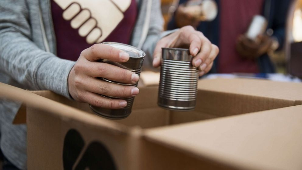 An undated stock photo depicts people packing boxes with canned food.