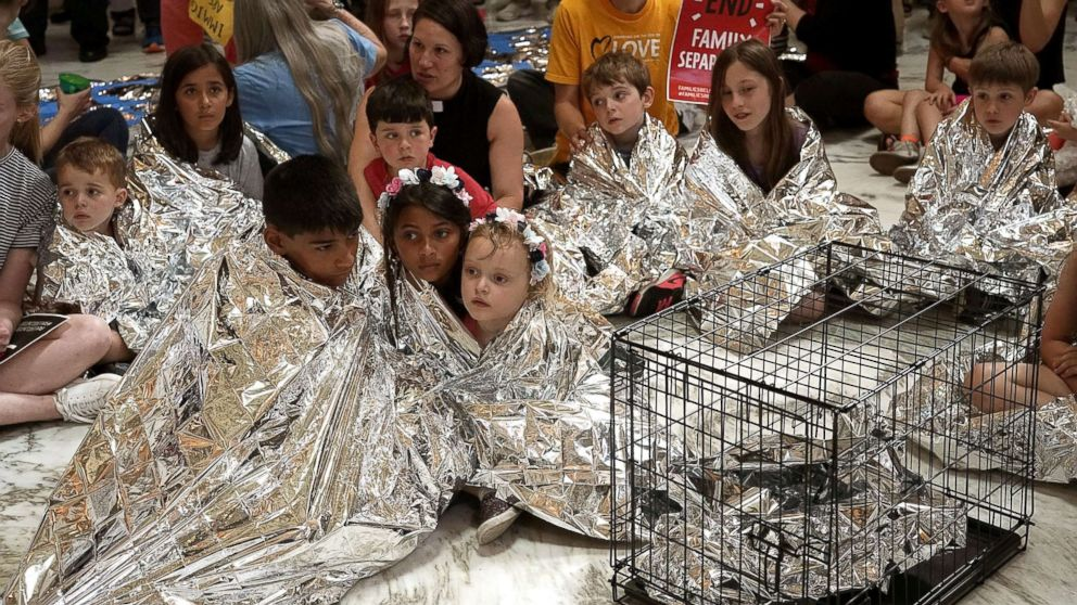 Children wrap themselves up with Mylar blankets to 'symbolically represent the thousands of children separated from families on the border, sleeping on floors and held in cages', during a protest at the rotunda of Russell Senate Office Building June 21, 2018 on Capitol Hill in Washington, D.C. Activists staged a demonstration to protest the Trump Administration's policy to separate migrant families at the southern border.