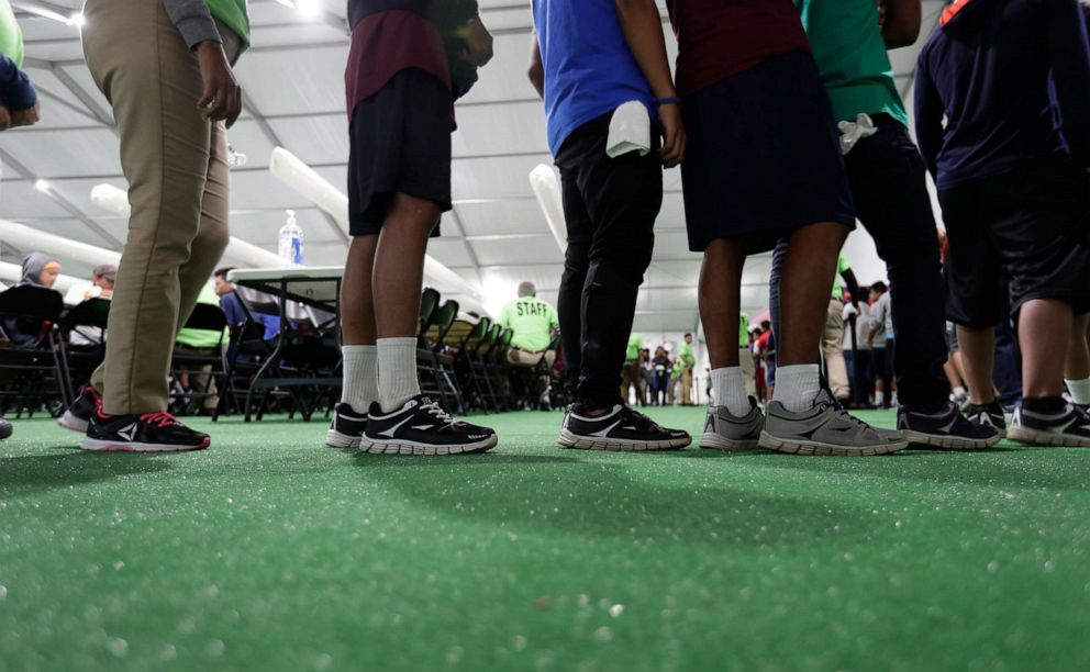 PHOTO: In this July 9, 2019 photo, immigrants line up in the dinning hall at the U.S. governments newest holding center for migrant children in Carrizo Springs, Texas.