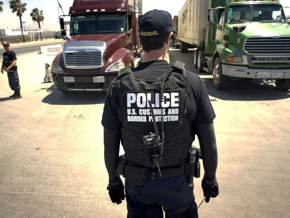 PHOTO: A U.S. Customs and Border Protection (CBP) officer stands in front of a line of trucks that will undergo a secondary inspection at the Otay Mesa Cargo Port of Entry in San Diego, on May 23, 2017.