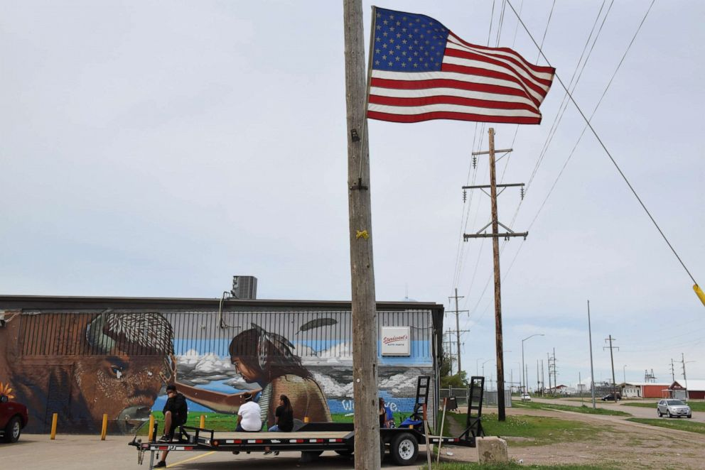 PHOTO: People sit in front of a mural depicting a buffalo and a Native American man along the main road on the Cheyenne River Reservation in Eagle Butte, S.D., May 28, 2018.
