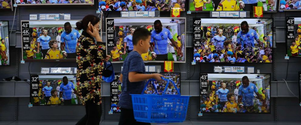 PHOTO: A woman and a child pass Chinese brands of flat screen TVs on display at a hypermarket in Beijing, July 11, 2018.