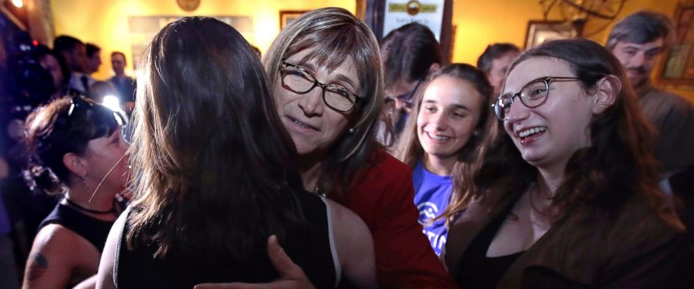 Vermont Democratic gubernatorial candidate Christine Hallquist, center, a transgender woman and former electric company executive, embraces supporters after claiming victory during her election night party in Burlington, Vt., Tuesday, Aug. 14, 2018.