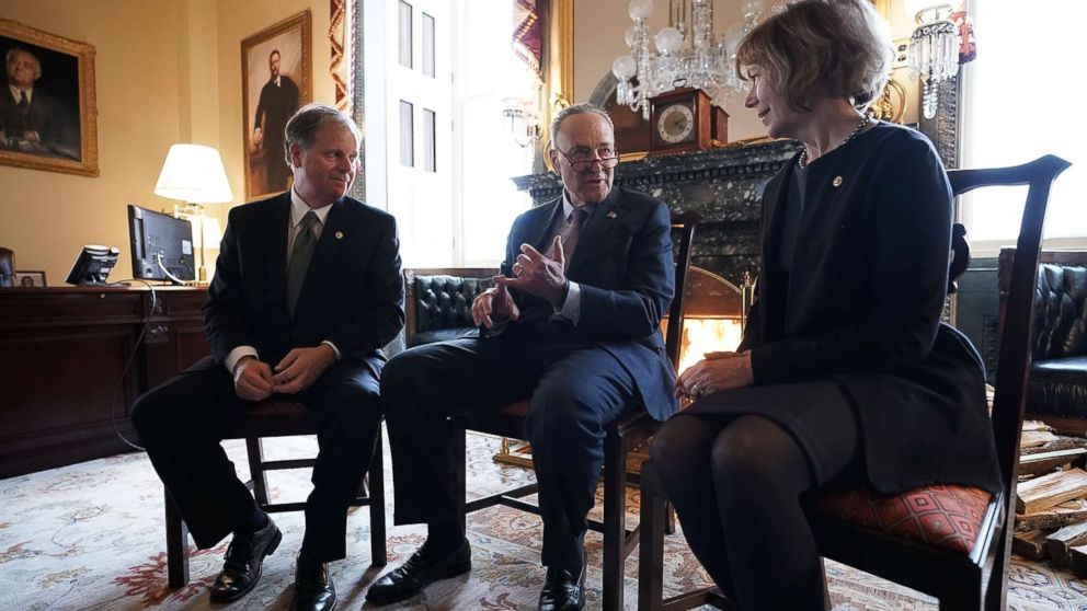 Senate Minority Leader Chuck Schumer, center, speaks to Sen. Doug Jones and Sen. Tina Smith during a meeting at the U.S. Capitol, Jan. 3, 2018, in Washington.