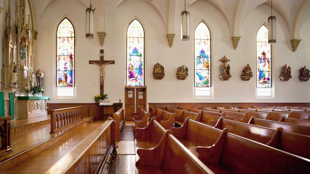 An undated stock photo of pews and stained glass windows in a church.