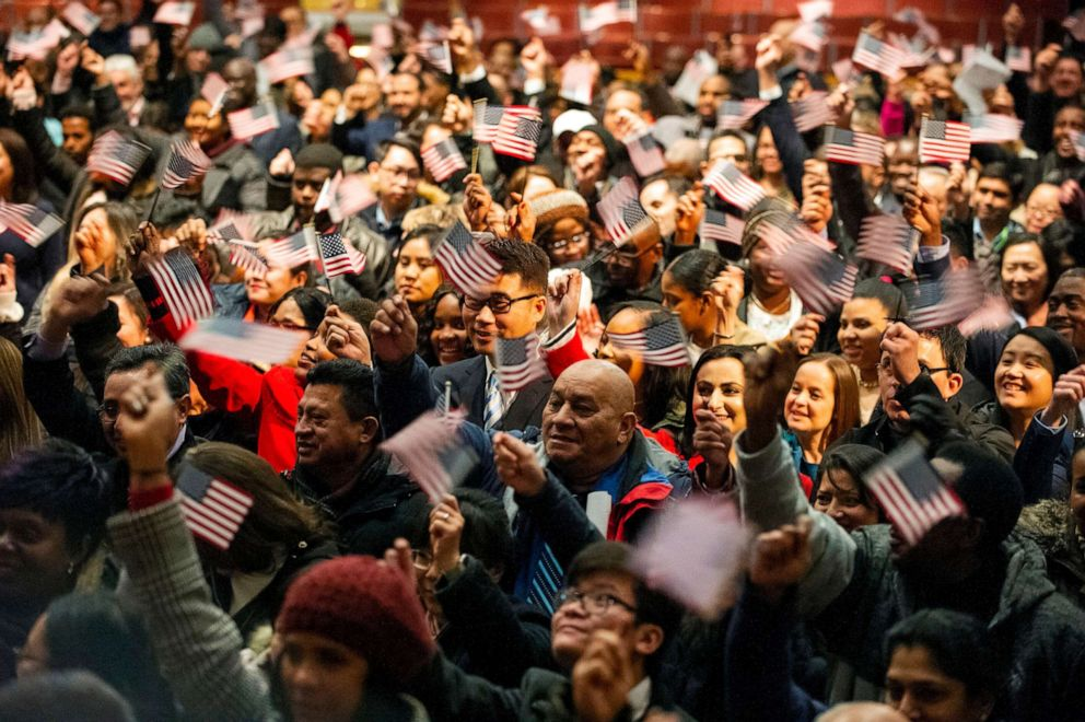 PHOTO: In this Januaruy 22, 2019, file photo, newly sworn-in U.S. citizens celebrate and wave US flags during a naturalization ceremony where 633 immigrants became US citizens,at the Lowell Auditorium, in Lowell, Massachusetts.