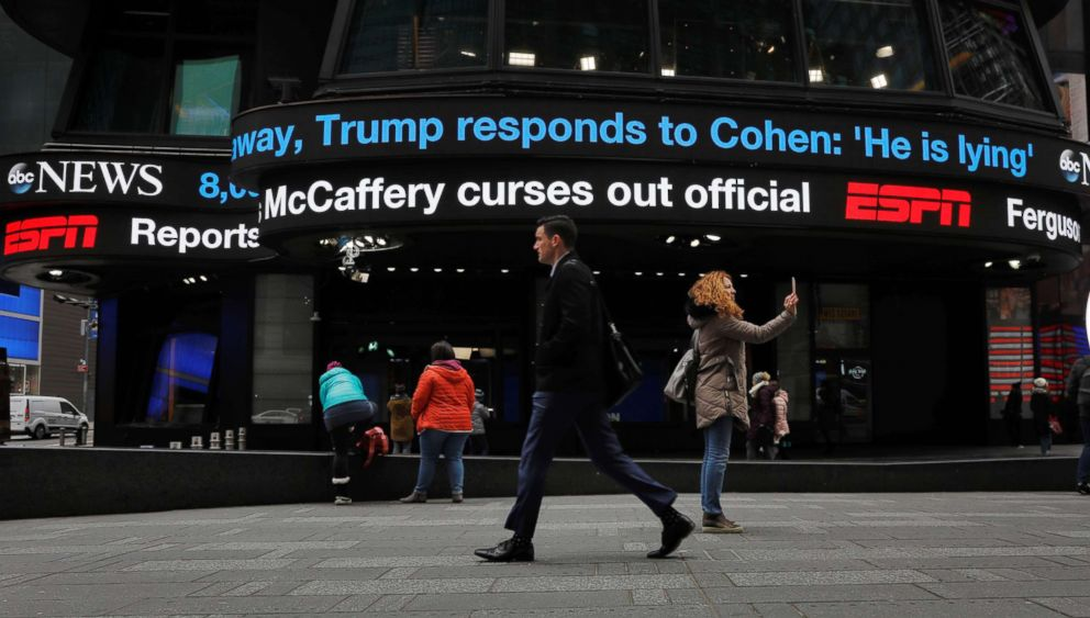 PHOTO: Pedestrians walk past a news banner in the Times Square, New York as it references Michael Cohen, the former personal attorney of President Donald Trump, as he testifies before Congress, Feb. 27, 2019.