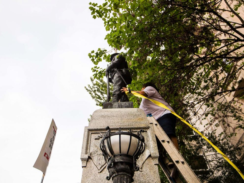 PHOTO: An unidentified protester climbs a ladder to place a rope around a Confederate statue during a rally Monday, Aug. 14, 2017, in Durham, N.C.
