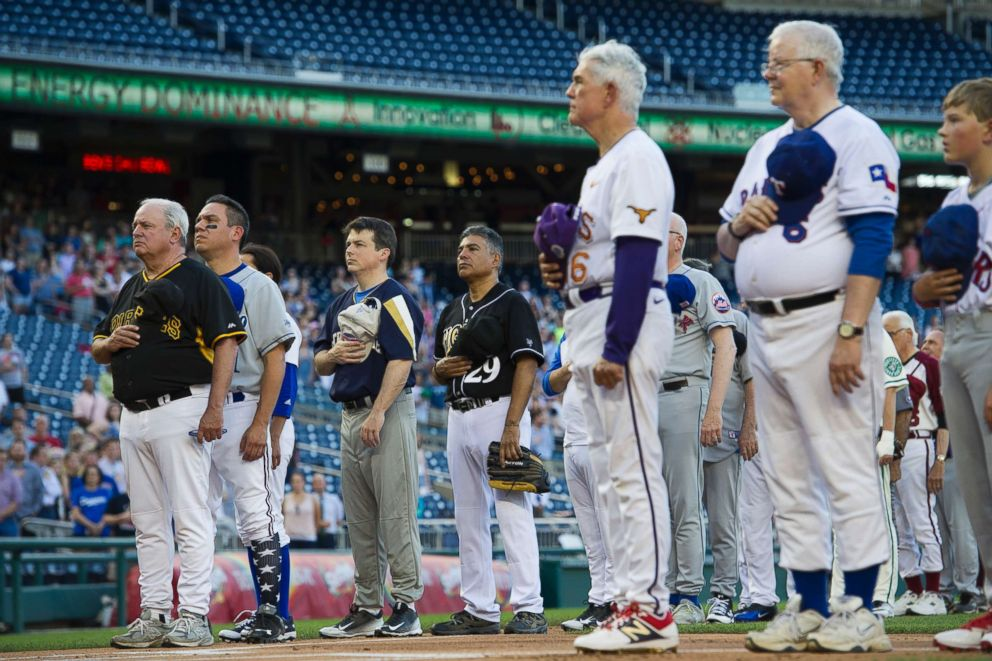 PHOTO: Members of the Democratic and Republican baseball teams stand for the national anthem to start the 57th Congressional Baseball Game at Nationals Park in Washington, June 14, 2018.