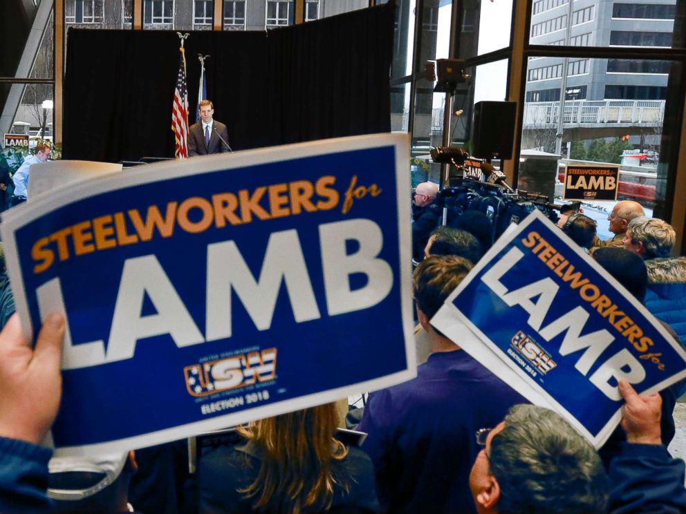 PHOTO: Democrat Conor Lamb, top, addresses the crowd as they hold signs of support during a campaign rally at the United Steelworkers headquarters in Pittsburgh, March 9, 2018.