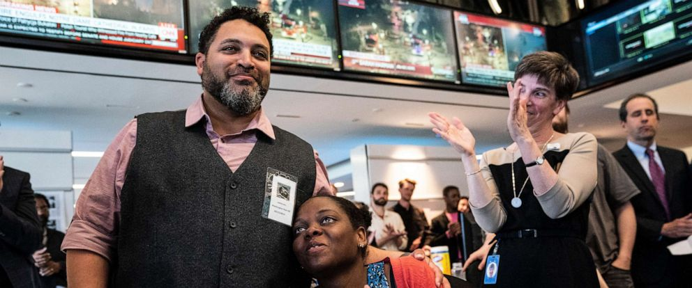 PHOTO: Darrin Bell hugs his wife Makeda Rashidi after winning a Pulitzer Prize for Editorial Cartooning during a 2019 Pulitzer Prize announcement ceremony in the newsroom at the Washington Post office on April 15, 2019 in Washington.