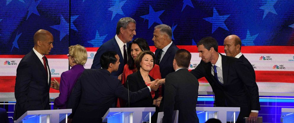 PHOTO: Democratic presidential hopefuls greet each other at the end of the first night of the Democratic presidential primary debate hosted by NBC News at the Adrienne Arsht Center for the Performing Arts in Miami, June 26, 2019.