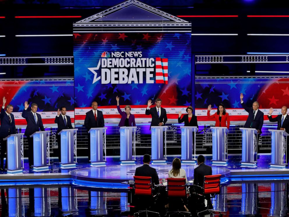 PHOTO: All candidates except Senator Cory Booker raise their hands while responding to a question during the first 2020 presidential election Democratic candidates debate in Miami, June 26, 2019.