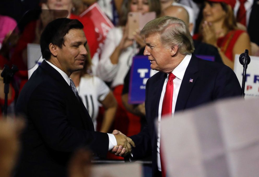 Florida Republican gubernatorial candidate Ron DeSantis shakes hands with President Donald Trump, July 31, 2018, during a rally in Tampa, Fla.