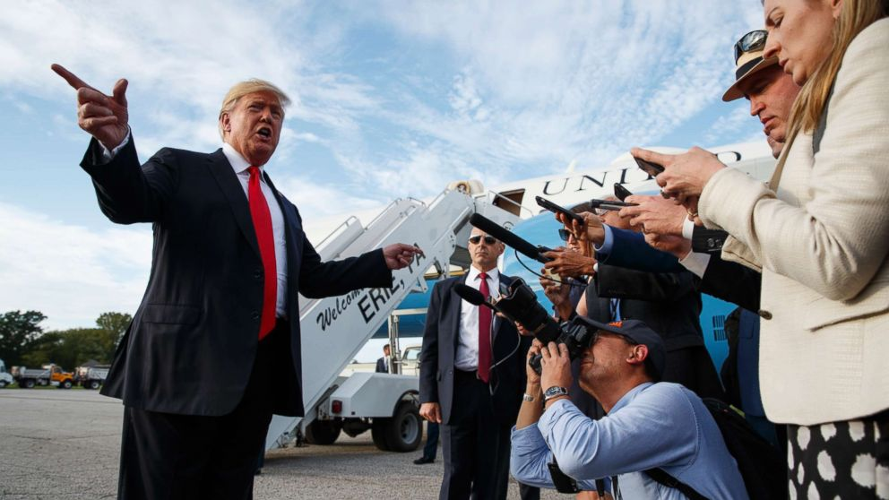 President Donald Trump talks with reporters after arriving at Erie International Airport for a campaign rally at Erie Insurance Arena, Oct. 10, 2018, in Erie, Pa.