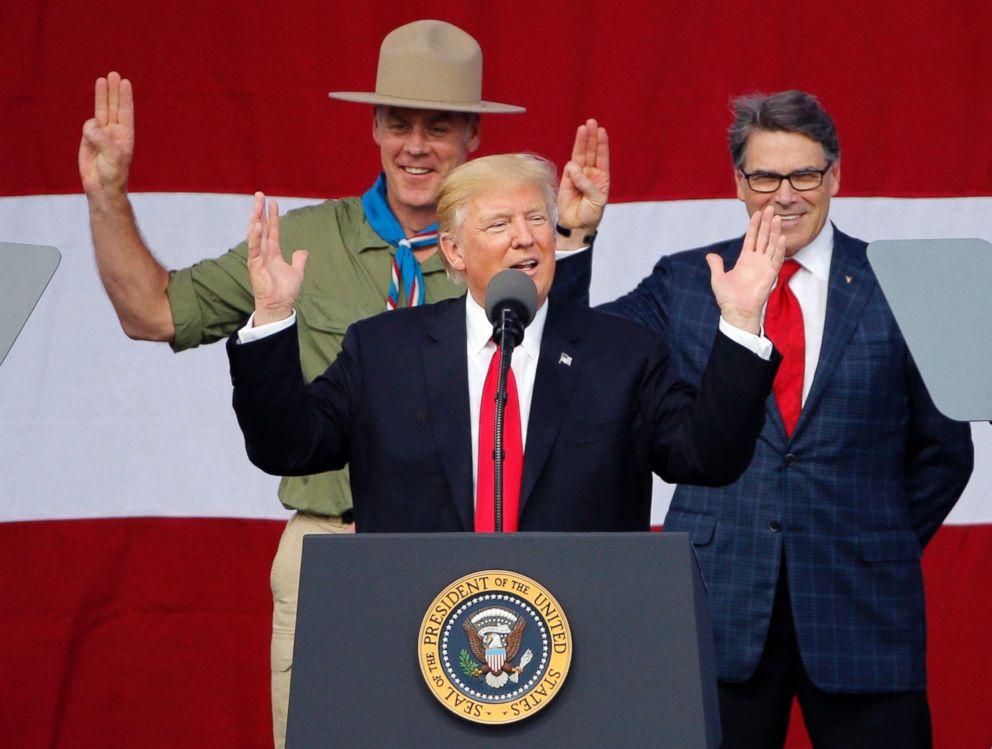 President Donald Trump gestures as former boys scouts, Interior Secretary Ryan Zinke, left, Energy Secretary Rick Perry, watch at the 2017 National Boy Scout Jamboree at the Summit in Glen Jean, W. Va., July 24, 2017.