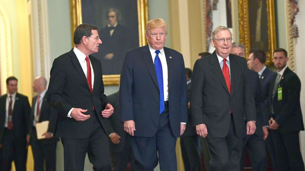 President Donald Trump, walks with Sen. John Barrasso, left, and Senate Majority Leader Mitch McConnell, right, as he arrives on Capitol Hill in Washington, Nov. 28, 2017.