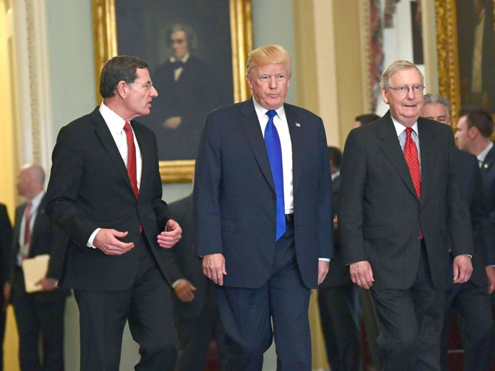 PHOTO: President Donald Trump, walks with Sen. John Barrasso, left, and Senate Majority Leader Mitch McConnell, right, as he arrives on Capitol Hill in Washington, Nov. 28, 2017.
