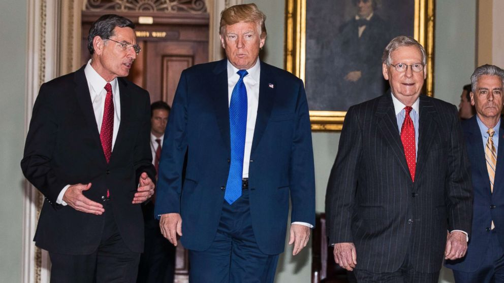 President Donald Trump along with Republican Senator from Wyoming John Barrasso (L) and Republican Senate Majority Leader from Kentucky Mitch McConnell (R), walk to a Republican Senate luncheon where the president is expected to push Senators on tax reform in the U.S. Capitol on Nov. 28 2017.