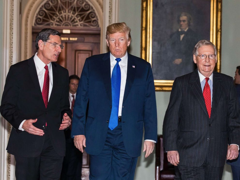 PHOTO: President Donald Trump along with Republican Senator from Wyoming John Barrasso (L) and Republican Senate Majority Leader from Kentucky Mitch McConnell (R), walk to a Republican Senate luncheon in the U.S. Capitol on Nov. 28 2017.